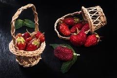 Fresa roja madura fresca en una cesta de madera y baya asperjada en el fondo negro Fotografía de archivo
