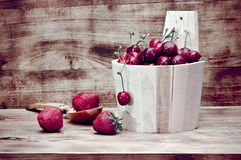 Fresa y cereza en una tabla de madera imagenes de archivo