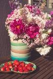 Fresa y ramo de flores blancas y violetas rosadas Fotos de archivo