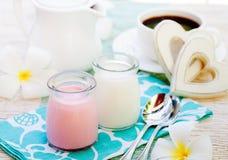 Fresa y vainilla hechas en casa del yogur en fondo romántico del desayuno de los tarros del vidrio con el corazón de madera imagenes de archivo