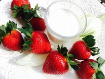 Fresa y vidrio de leche en la placa blanca Fotos de archivo