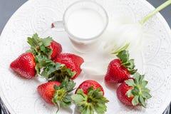 Fresa y vidrio de leche en la placa blanca Foto de archivo