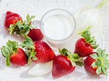 Fresa y vidrio de leche en la placa blanca Foto de archivo libre de regalías