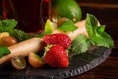 Fresas, cal, menta y uvas brillantes, maduras, deliciosas con un triturador del cóctel en el escritorio negro Frutas del verano B Imagenes de archivo