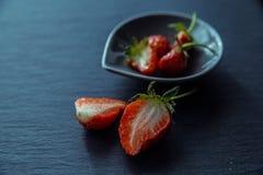 Fresas cortadas en la placa negra foto de archivo libre de regalías