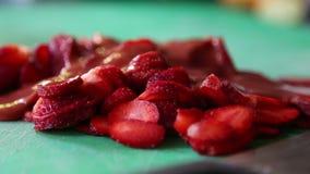 Fresas cortadas en una tajadera verde, con el cuchillo a un lado metrajes