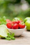 Fresas dulces sabrosas frescas y cal verde al aire libre en verano imágenes de archivo libres de regalías