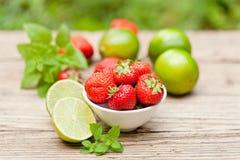 Fresas dulces sabrosas frescas y cal verde al aire libre en verano foto de archivo libre de regalías