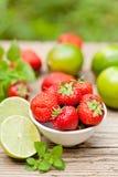 Fresas dulces sabrosas frescas y cal verde al aire libre en verano imagen de archivo