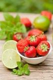 Fresas dulces sabrosas frescas y cal verde al aire libre en verano fotografía de archivo libre de regalías