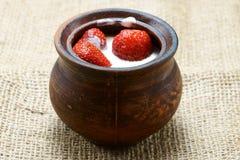 Fresas en crema en mercancías de la arcilla en harpillera Imagen de archivo libre de regalías