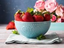 Fresas en cuenco con el corazón y las rosas Foto de archivo libre de regalías
