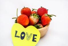 Fresas en cuenco de madera con la nota del amor Foto de archivo libre de regalías