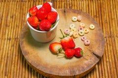 Fresas en taza, al tajar la madera, fondo de la rota, f selecta Foto de archivo libre de regalías