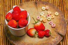 Fresas en taza, al tajar la madera, fondo de la rota, f selecta Imágenes de archivo libres de regalías