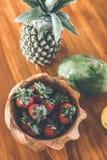 Fresas en un cuenco de madera de la teca Cuenco indonesio de la teca foto de archivo