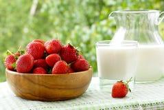 Fresas en un cuenco de madera, un vidrio y un jarro de leche Foto de archivo libre de regalías