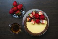 Fresas en un platillo en el fondo de un pastel de queso standDecorated de madera de la fresa con una taza de té y de fresas imágenes de archivo libres de regalías