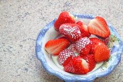Fresas en un plato con crema Foto de archivo libre de regalías
