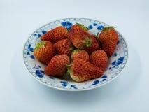 Fresas en un plato de porcelana azul y blanco, aislado en el fondo blanco imagen de archivo