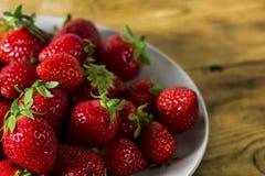 Fresas en un plato en la tabla rústica Imagen de archivo libre de regalías