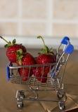 Fresas en una carretilla azul de las compras fotografía de archivo libre de regalías