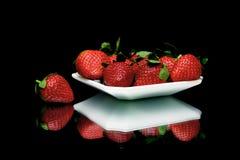 Fresas en una placa en un fondo negro con el reflec del espejo Imagenes de archivo