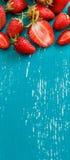 Fresas en una tabla de madera de los azules turquesa Foto de archivo