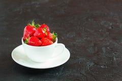Fresas en una taza blanca en un fondo oscuro Fotos de archivo libres de regalías
