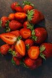 Fresas enteras y cortadas frescas en una tabla oscura imagenes de archivo