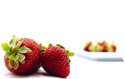 Two strawberries and a plate stock images