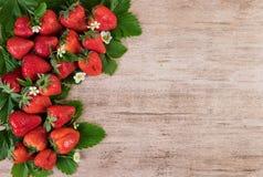 Fresas frescas con las hojas sobre fondo de madera con el espacio de la copia Imágenes de archivo libres de regalías