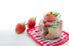 Fresas frescas en el tarro de cristal en el fondo de madera blanco con el SE Fotografía de archivo libre de regalías