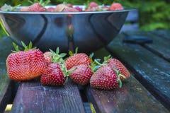 Fresas frescas en un cuenco en una tabla de madera Fotos de archivo libres de regalías