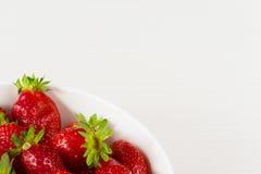 Fresas frescas rojas en un cuenco aislado en el fondo blanco Ciérrese encima de la visión Imagen de archivo