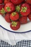 Fresas jugosas frescas en la loza del enamelware del vintage en rusti Foto de archivo