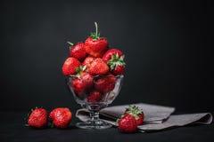 Fresas jugosas maduras en un vidrio en un fondo oscuro Imagen de archivo libre de regalías
