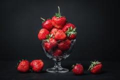 Fresas jugosas maduras en un vidrio en un fondo oscuro Fotos de archivo libres de regalías