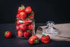 Fresas jugosas maduras en un vidrio en un fondo oscuro Foto de archivo