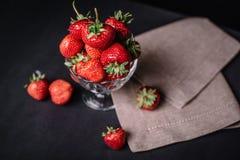 Fresas jugosas maduras en un vidrio en un fondo oscuro Imagen de archivo