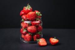 Fresas jugosas maduras en un vidrio en un fondo oscuro Imagenes de archivo