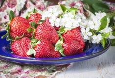 Fresas maduras adornadas con las cerezas de las flores frescas, en la madera Imágenes de archivo libres de regalías
