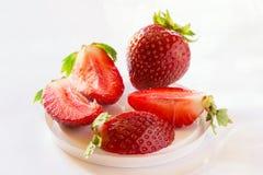 Fresas maduras dulces y un conjunto y un corte en los pedazos que mienten en la tabla en una alta llave Foto de archivo libre de regalías