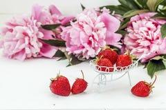 Fresas maduras en una carretilla decorativa del jardín en un fondo Foto de archivo libre de regalías