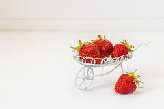Fresas maduras en una carretilla decorativa del jardín en una parte posterior del blanco Fotos de archivo libres de regalías