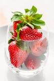 Fresas maduras en una placa blanca en un vidrio en un fondo ligero Imágenes de archivo libres de regalías