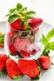 Fresas maduras en una placa en un vidrio y una puntilla de la menta en un fondo ligero Imagen de archivo