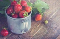 Fresas maduras en una taza del metal Vector de madera viejo Fotografía de archivo libre de regalías