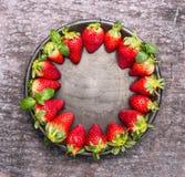 Fresas maduras frescas en placa en el fondo de madera gris, marco de la comida, visión superior Imagen de archivo