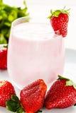 Fresas maduras grandes y un vidrio de yogur de consumición en un fondo ligero Imagen de archivo